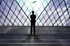 Homem de negócios que olha o embarque do avião nas partidas g do aeroporto imagens de stock royalty free