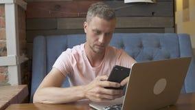 Homem de negócios que olha o smartphone ao trabalhar em um portátil video estoque