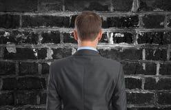 Homem de negócios que olha a parede de tijolo fotos de stock royalty free