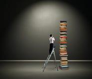 Homem de negócios que olha a pilha dos livros Foto de Stock Royalty Free