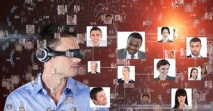 Homem de negócios que olha retratos através dos fones de ouvido de VR Imagens de Stock