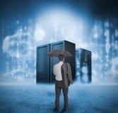 Homem de negócios que olha servidores azuis Imagens de Stock