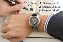 Homem de negócios que olha seu relógio que sugere a falta de hora de cumprir todas suas tarefas escritas na agenda fotos de stock royalty free