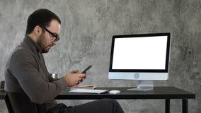 Homem de negócios que olha sua mensagem do smartphone e que senta-se perto do tela de computador Indicador branco fotografia de stock