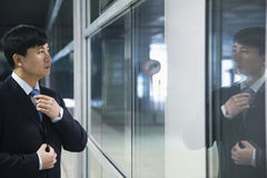 Homem de negócios que olha sua reflexão e que ajusta seu laço Foto de Stock Royalty Free