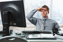 Homem de negócios que olha a tela no escritório Imagem de Stock
