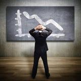 Homem de negócios que olha um diagrama deixando cair Foto de Stock Royalty Free