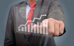 Homem de negócios que olha um gráfico do sucesso Foto de Stock Royalty Free