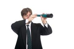 Homem de negócios que olha um spyglass foto de stock