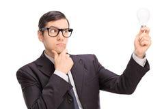 Homem de negócios que olha uma ampola e um pensamento Imagens de Stock Royalty Free