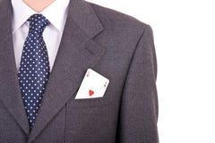 Homem de negócios que põe o cartão do ás em seu bolso. Fotografia de Stock Royalty Free