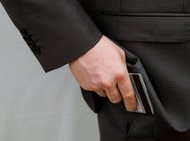 Homem de negócios que põe um cartão de crédito em um bolso imagem de stock