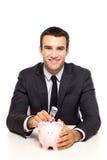Homem de negócios que põr o dinheiro no banco piggy imagem de stock royalty free
