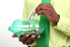 Homem de negócios que põr um dólar Bill no banco Piggy verde imagem de stock