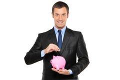Homem de negócios que põr uma moeda em um banco piggy Foto de Stock Royalty Free