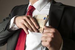Homem de negócios que pôr o dinheiro no bolso Fotografia de Stock Royalty Free