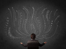 Homem de negócios que pensa com setas esboçadas na frente de um chalkboa Imagens de Stock