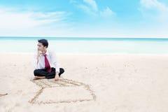 Homem de negócios que pensa em uma praia Fotografia de Stock Royalty Free