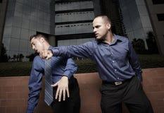 Homem de negócios que perfura um outro homem de negócios imagens de stock royalty free