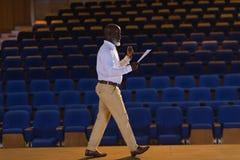 Homem de negócios que pratica e que aprende o roteiro ao andar no auditório fotos de stock royalty free