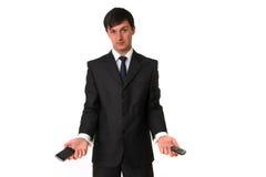 Homem de negócios que prende dois telefones móveis Fotos de Stock