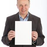 Homem de negócios que prende o cartão branco em branco imagem de stock