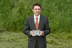 Homem de negócios que prende o cartão cinzento foto de stock