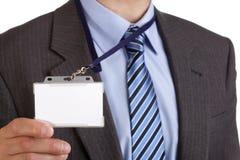 Homem de negócios que prende o emblema em branco da identificação Foto de Stock Royalty Free