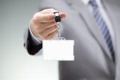 Homem de negócios que prende o emblema em branco da identificação fotografia de stock royalty free