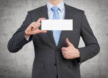 Homem de negócios que prende o poster em branco Imagem de Stock