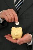 Homem de negócios que prende um banco Piggy Foto de Stock