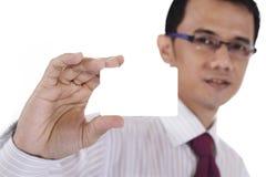 Homem de negócios que prende um cartão em branco Fotografia de Stock Royalty Free