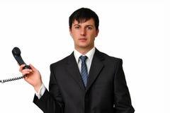 Homem de negócios que prende um receptor do telefone Imagem de Stock