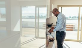 Homem de negócios que prepara o café da manhã em casa foto de stock royalty free