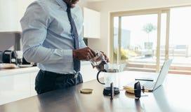 Homem de negócios que prepara o café em casa imagens de stock