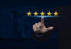 Homem de negócios que pressiona cinco estrelas do ouro para aumentar a avaliação sobre o mapa Fotografia de Stock Royalty Free