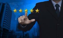 Homem de negócios que pressiona cinco estrelas do ouro para aumentar a avaliação sobre o mapa Imagem de Stock Royalty Free