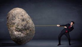 Homem de negócios que puxa a rocha enorme com uma corda Fotos de Stock Royalty Free