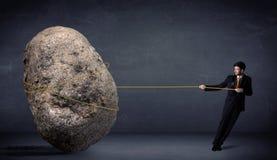 Homem de negócios que puxa a rocha enorme com uma corda ilustração stock