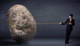 Homem de negócios que puxa a rocha enorme com uma corda ilustração do vetor