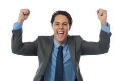 Homem de negócios que rasing seus braços e que cheering alegre Fotografia de Stock