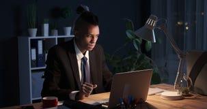 Homem de negócios que recebe a notícia negativa no portátil no escritório da noite vídeos de arquivo