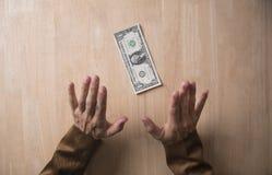 Homem de negócios que recusa o dinheiro de um subôrno na tabela de madeira Fotos de Stock
