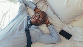 Homem de negócios que relaxa na cama foto de stock