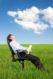 Homem de negócios que relaxa na pastagem sob o céu azul Imagem de Stock Royalty Free