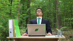 Homem de negócios que respira profundamente o ar fresco no escritório eco-amigável, trabalhando no portátil vídeos de arquivo