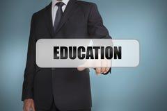 Homem de negócios que seleciona a educação da palavra escrita na etiqueta branca Imagens de Stock