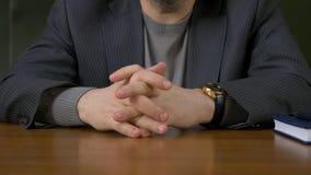 Homem de negócios que senta-se com dedos cruzados Homem de negócios que senta-se na tabela com os dedos cruzados Fotos de Stock Royalty Free