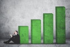 Homem de negócios que senta-se com gráfico da finança do crescimento imagens de stock royalty free