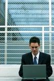 Homem de negócios que senta-se com portátil foto de stock royalty free